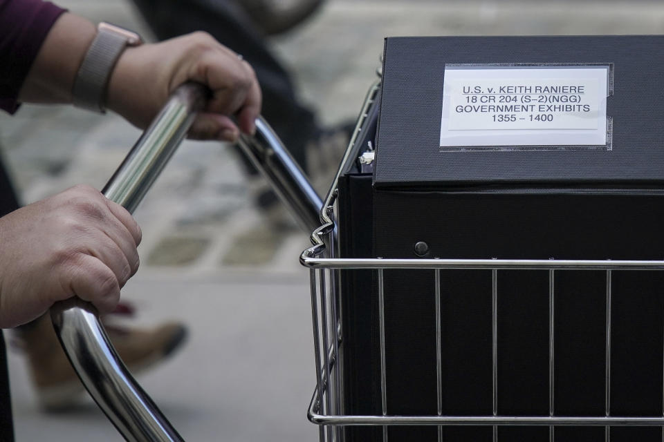 a close up photo of a woman's hands pushing a trolley full of court documents related to the U.S. v. Keith Raniere case at the U.S. District Court for the Eastern District of New York a, May 7, 2019 in the Brooklyn borough of New York City.