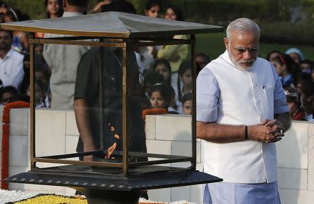 India's Prime Minister Modi walks after paying homage at the Mahatma Gandhi memorial on the 145th birth anniversary of Gandhi at Rajghat in New Delhi