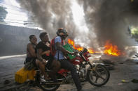 A moto-taxi driver takes two women past a burning barricade set up by people protesting fuel shortages in Petion-ville, Haiti, Sept. 15, 2019. The image was part of a series of photographs by Associated Press photographers which was named a finalist for the 2020 Pulitzer Prize for Breaking News Photography. (AP Photo/Dieu Nalio Chery)