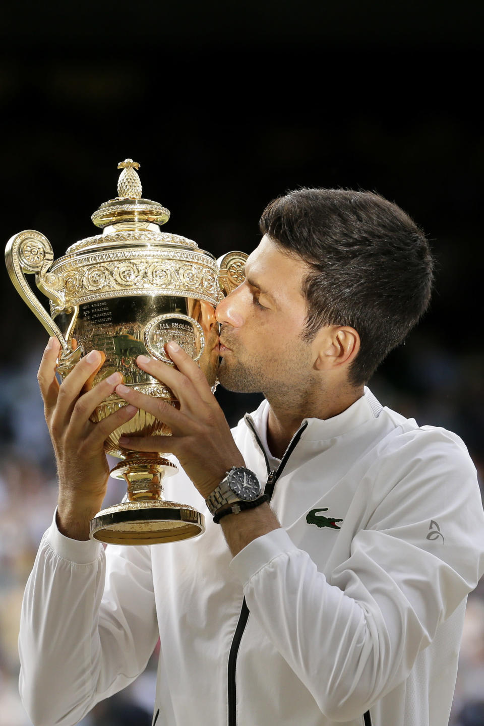 FILE - In this July 14, 2019, file photo, Serbia's Novak Djokovic kisses the trophy after defeating Switzerland's Roger Federer in the men's singles final match of the Wimbledon Tennis Championships in London. Federer leads the list with 20 Grand Slam singles titles. Rafael Nadal has 19. Djokovic has 16. (AP Photo/Tim Ireland, File)
