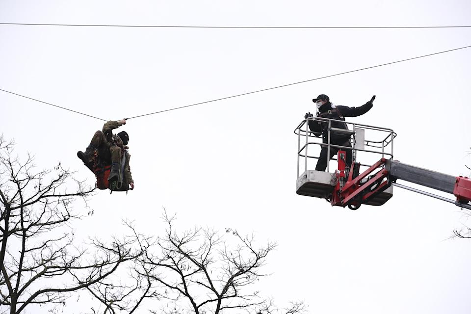 An enforcement officer approaches a HS2 Rebellion protester on a zip line between two trees in an encampment in Euston Square Gardens in central London, where the protesters have built a 100ft tunnel network, which they are ready to occupy, after claiming the garden is at risk from the HS2 line development. The spire of St Pancras New Church is in the background. Picture date: Wednesday January 27, 2021.