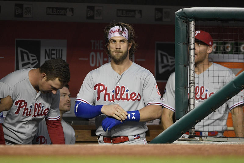 Philadelphia Phillies' Bryce Harper, center, stands in the dugout before a baseball game against the Washington Nationals, Monday, Sept. 23, 2019, in Washington. (AP Photo/Nick Wass)