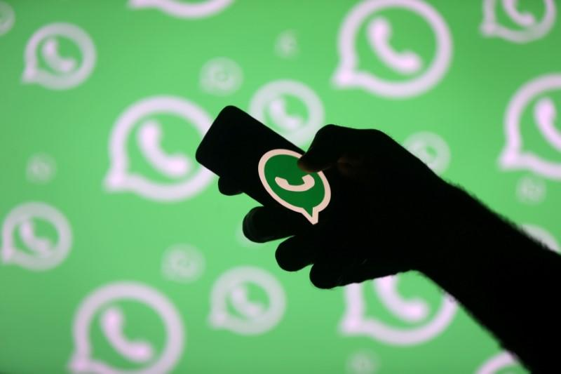 FILE PHOTO: A man poses with a smartphone in front of displayed Whatsapp logo in this illustration