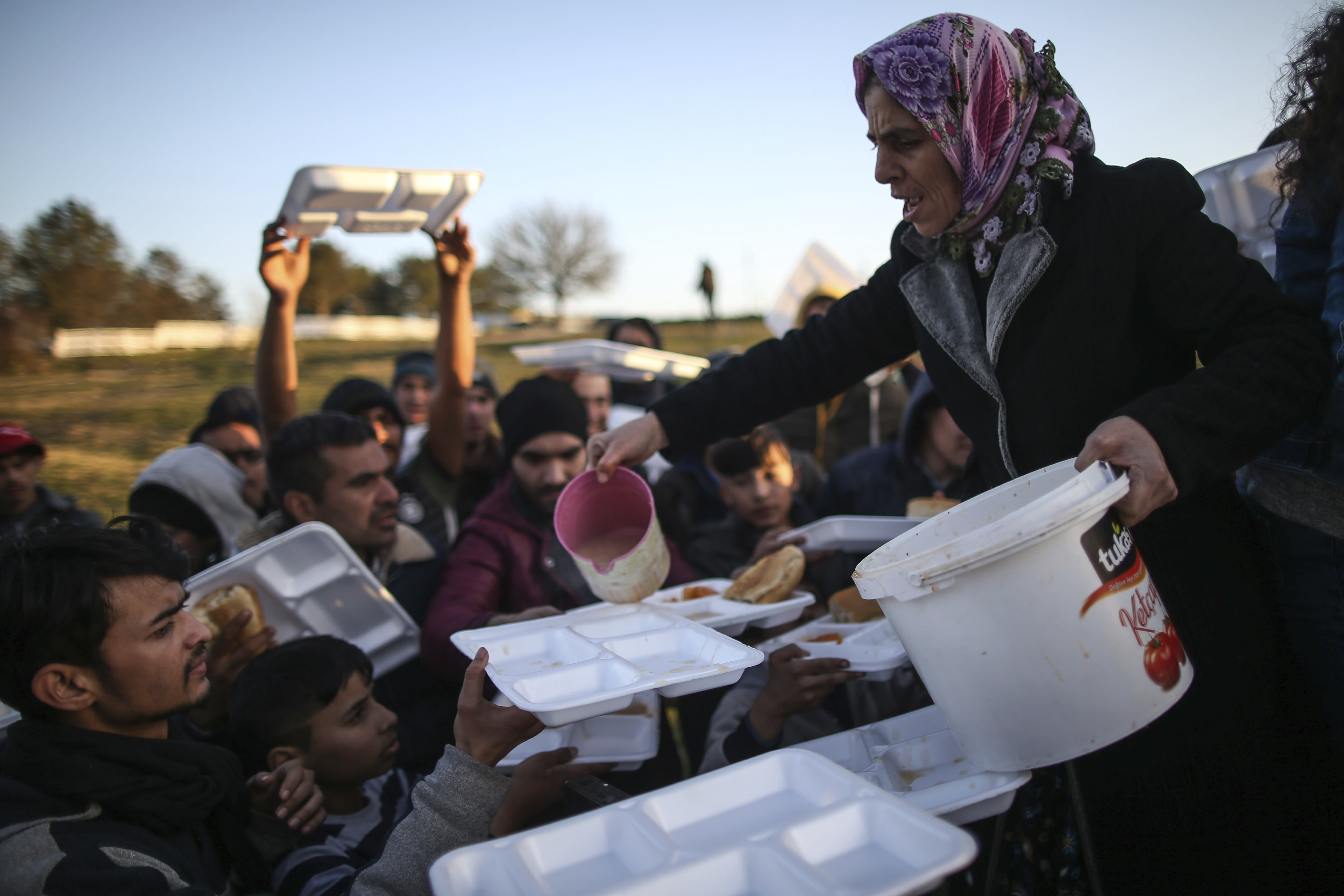 Migrants receive food as they gather in a field near Edirne, at the Turkish-Greek border on Monday, March 2, 2020. Thousands of migrants on Monday tried to find a way across the land border into Greece, which has made clear its borders will remain closed. Dozens managed to pass, either through border fences or across the river there. (AP Photo/Emrah Gurel)