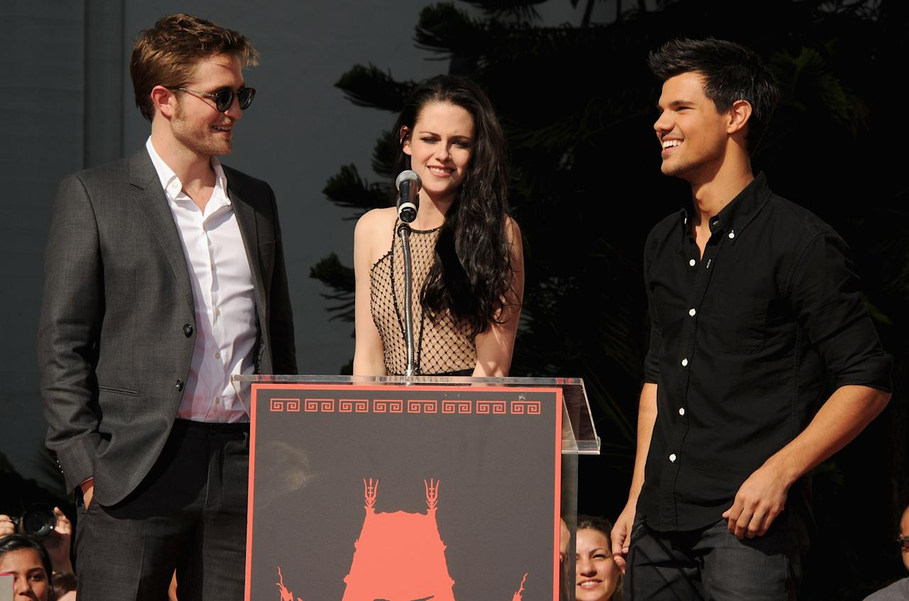 HOLLYWOOD, CA - NOVEMBER 03:  (L-R) Actors Robert Pattinson, Kristen Stewart and Taylor Lautner are Immortalized in a Hand and Footprint Ceremony at the Grauman's Chinese Theatre on November 3, 2011 in Hollywood, California.  (Photo by Kevin Winter/Getty Images)