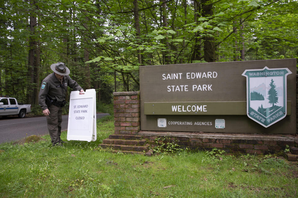 KENMORE, WA - MAY 05: Daryl Kline, a park ranger at Saint Edward State Park removes a sign saying the park is closed on May 5, 2020 in Kenmore, Washington. The first phase to reopen the state begins today easing some restrictions that were put in place during Governor Jay Inslees Stay Home, Stay Healthy order last March to help reduce the spread of COVID-19. Kenmore, WA is located northeast of Seattle. (Photo by Karen Ducey/Getty Images)