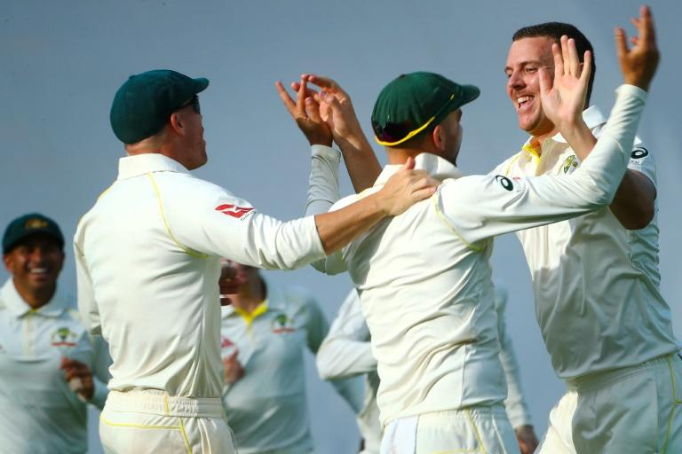 Australia's bowler Josh Hazlewood (R) celebrates with teammates David Warner and Nathan Lyon the run-out of England's batsman James Vince on the first day of their first Ashes Test, in Brisbane, on November 23, 2017