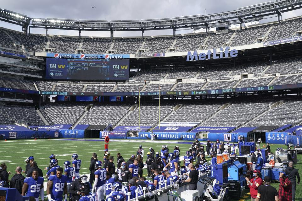 An empty MetLife stadium with the Giants on the sidelines.