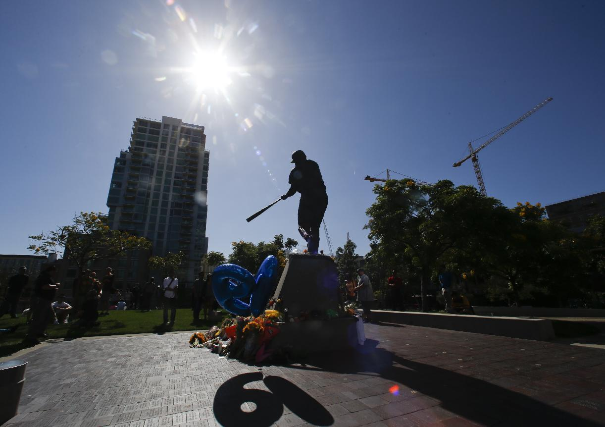 """The Tony Gwynn statue """"Mr.Padre"""" is silhouetted against the late afternoon sun as his number """"19""""  shines through balloons Monday, June 16, 2014, in San Diego. Gwynn, who won eight National League batting titles and was a member of the Baseball Hall of Fame, died Monday at 54 from cancer.  (AP Photo/Lenny Ignelzi)"""