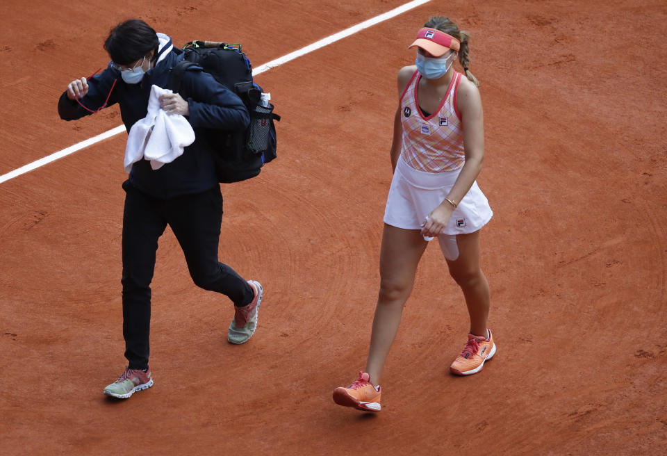 Sofia Kenin of the U.S. walks off the court to receive medical assistance in the final match of the French Open tennis tournament against Poland's Iga Swiatek at the Roland Garros stadium in Paris, France, Saturday, Oct. 10, 2020. (AP Photo/Alessandra Tarantino)
