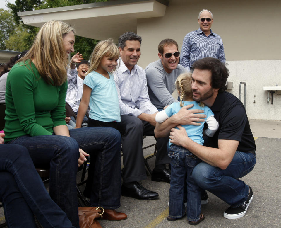FILE - In this Tuesday, Oct. 5, 2010, file photo, NASCAR driver Jimmie Johnson gets a hug from Addison Smith, 2, as her sister, Kylie, 5, and mother, Katie, look on at Emerald Middle School in his hometown of El Cajon, Calif. Johnson's foundation made a donation to the school. NASCAR's nicest guy will run his final race this week and close a remarkable career. Jimmie Johnson's record-tying seven Cup titles are well celebrated, but his charitable work goes less noticed. (AP Photo/Lenny Ignelzi, File)