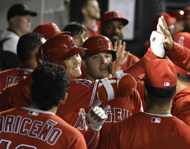 Los Angeles Angels' Shohei Ohtani, center left, is greeted by teammates after hitting a three-run home run against the Chicago White Sox during the third inning of a baseball game, Friday, Sept. 7, 2018, in Chicago. (AP Photo/David Banks)