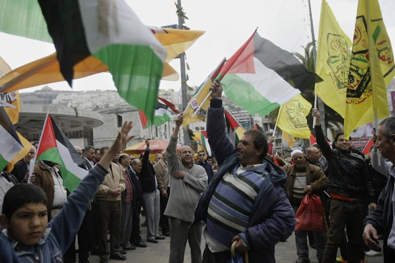 Palestinians wave its flags and Fatah's during a rally in support of Palestinian President Mahmoud Abbas in the West Bank city of Nablus on Wednesday, April 2, 2014. (AP Photo/Nasser Ishtayeh)