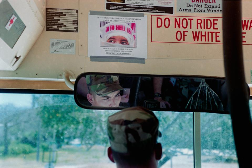 A bus driver is seen from behind.