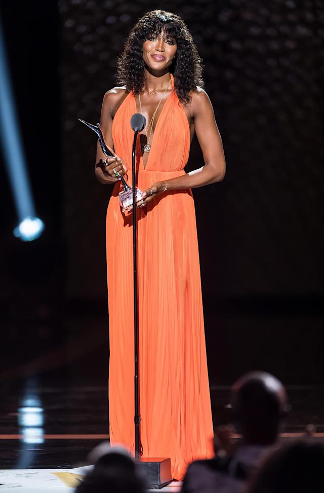 With natural, shoulder length hair and minimal make-up, Campbell accepted her award at the Black Girls Rock! Show in style. Usually sticking to more muted colours, this bright orange gown was an attention grabber, that's for sure. [Getty Images]