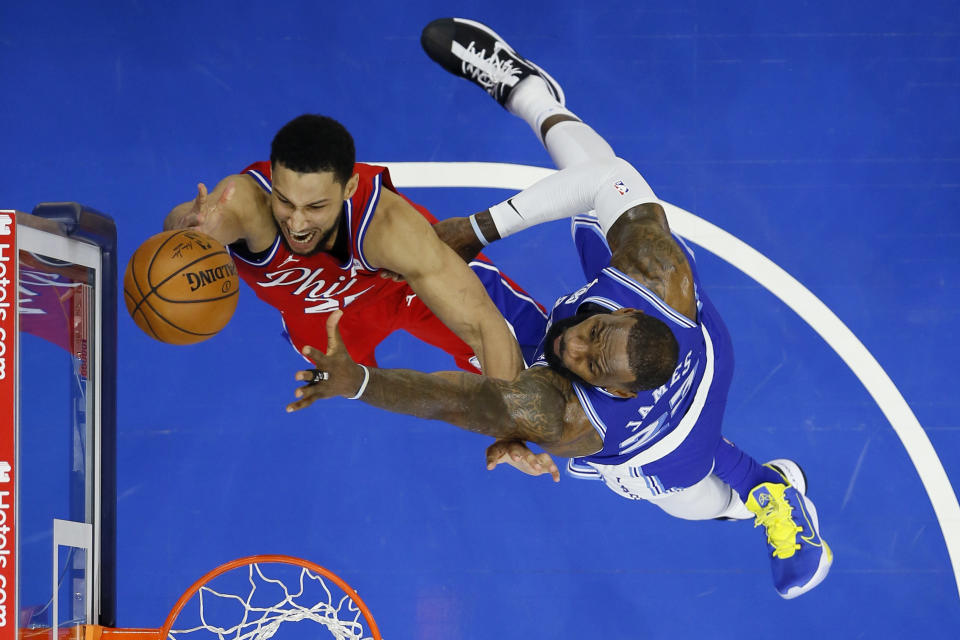 Philadelphia 76ers' Ben Simmons, left, goes up for a shot past Los Angeles Lakers' LeBron James during the first half of an NBA basketball game, Wednesday, Jan. 27, 2021, in Philadelphia. (AP Photo/Matt Slocum)