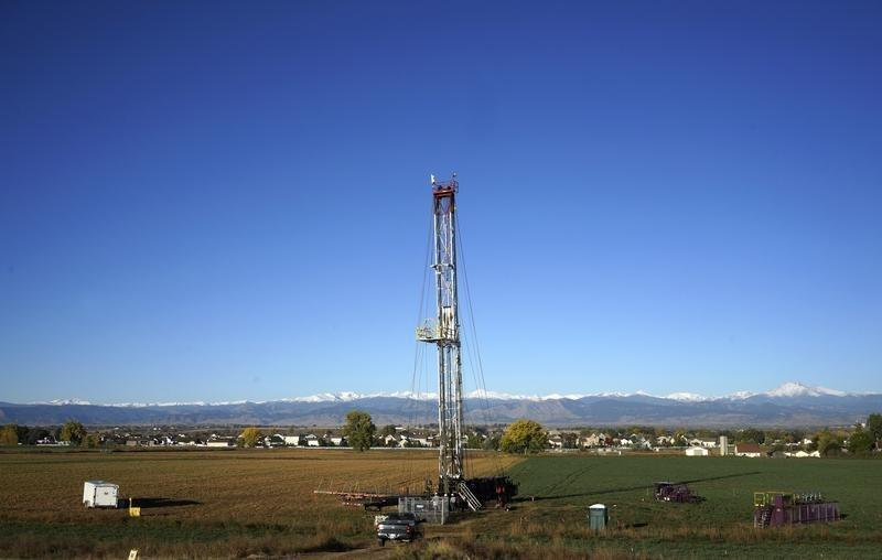 Workers drill a new oil well in a farm field within sight of houses near the town of Longmont