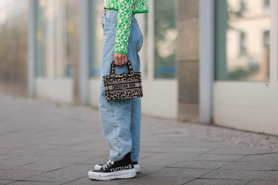 BERLIN, GERMANY - AUGUST 03: Sonia Lyson wearing Dior mini bag, green and white Zara cardigan, & other stories blue jeans and black Louis Vuitton sneakers on August 03, 2021 in Berlin, Germany. (Photo by Jeremy Moeller/Getty Images)