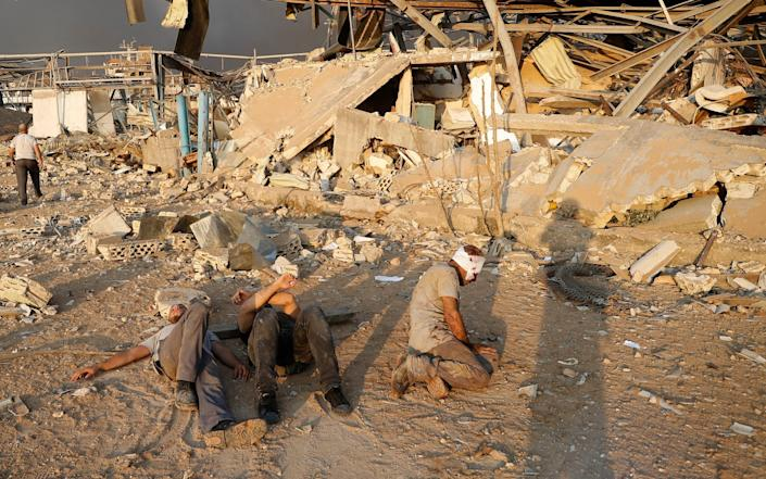 At the scene of the blast, injured men wait for help - AP