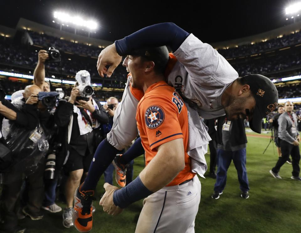 Alex Bregman lifts Jose Altuve as they celebrate after Game 7 of the World Series. (AP)