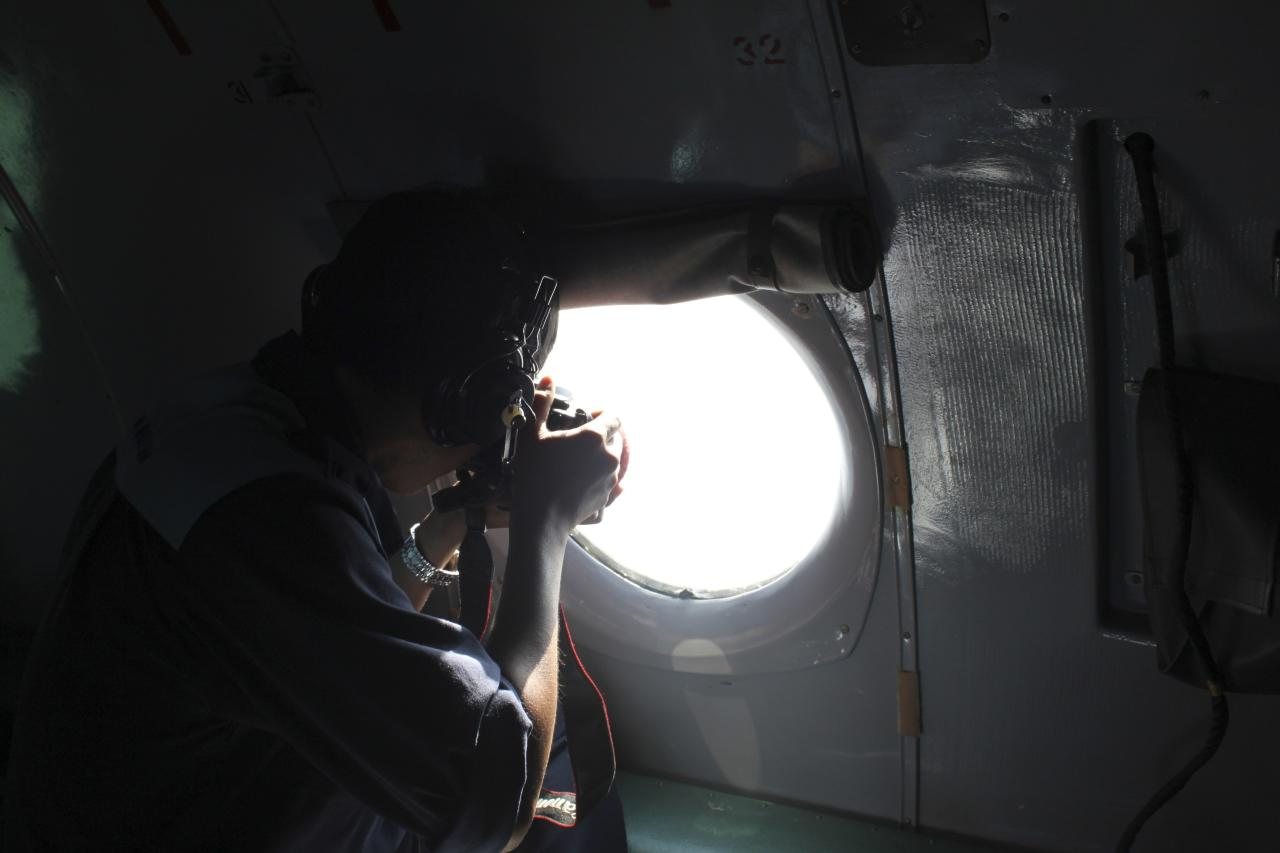A Vietnamese Air Force officer takes photos from a search and rescue aircraft in the search area for a missing Malaysia Airlines plane, 250 km from Vietnam and 190 km from Malaysia, in this handout photo from Thanh Nien Newpaper taken March 8, 2014. The Malaysia Airlines flight carrying 227 passengers and 12 crew went missing off the Vietnamese coast on Saturday as it flew from Kuala Lumpur to Beijing and was presumed to have crashed. There were no reports of bad weather and no sign why the Boeing 777-200ER, powered by Rolls-Royce Trent engines, would have vanished from radar screens about an hour after take-off. Mandatory Credit REUTERS/Trung Hieu/Thanh Nien Newspaper (VIETNAM - Tags: DISASTER TRANSPORT MILITARY) THIS IMAGE HAS BEEN SUPPLIED BY A THIRD PARTY. IT IS DISTRIBUTED, EXACTLY AS RECEIVED BY REUTERS, AS A SERVICE TO CLIENTS. NO SALES. NO ARCHIVES. FOR EDITORIAL USE ONLY. NOT FOR SALE FOR MARKETING OR ADVERTISING CAMPAIGNS. MANDATORY CREDIT. VIETNAM OUT. NO COMMERCIAL OR EDITORIAL SALES IN VIETNAM