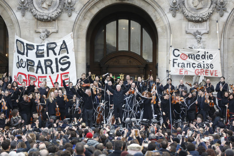Striking opera musicians wave to the crowd after performing outside the Palais Garnier opera house, Saturday, Jan. 18, 2020 in Paris. As some strikers return to work, with notable improvements for train services that have been severely disrupted for weeks, more radical protesters are trying to keep the movement going. Musicians, singers and other members of the striking Paris Opera drew a crowd with a free concert in front of the Palais Garnier opera house. (AP Photo/Thibault Camus)