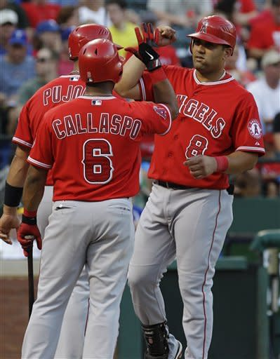 Los Angeles Angels designated hitter Kendrys Morales (8) is congratulated by Albert Pujols and Alberto Callaspo (6) at home plate after Morales' two-run home run during the sixth inning of a baseball game against the Texas Rangers, Monday, July 30, 2012, in Arlington, Texas. Pujols scored on the play. (AP Photo/LM Otero)
