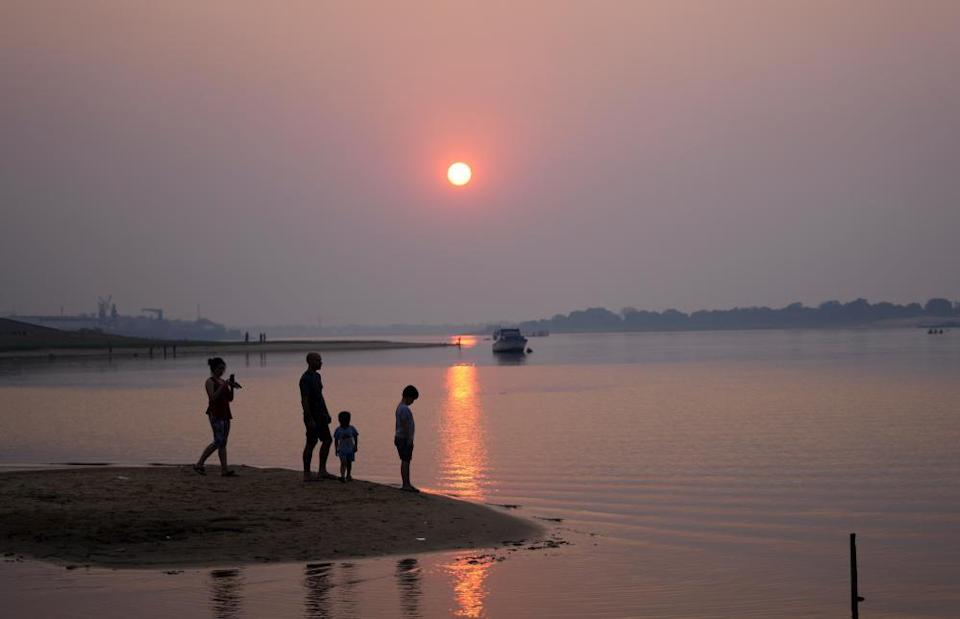 A family stands in the bay, connected to the Paraguay River in Asuncion, Paraguay, in August.