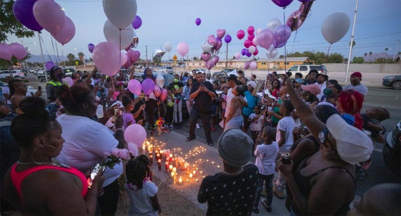 A crowd of people hold balloons around lit candles to remember one-year-old Sayah Deal.