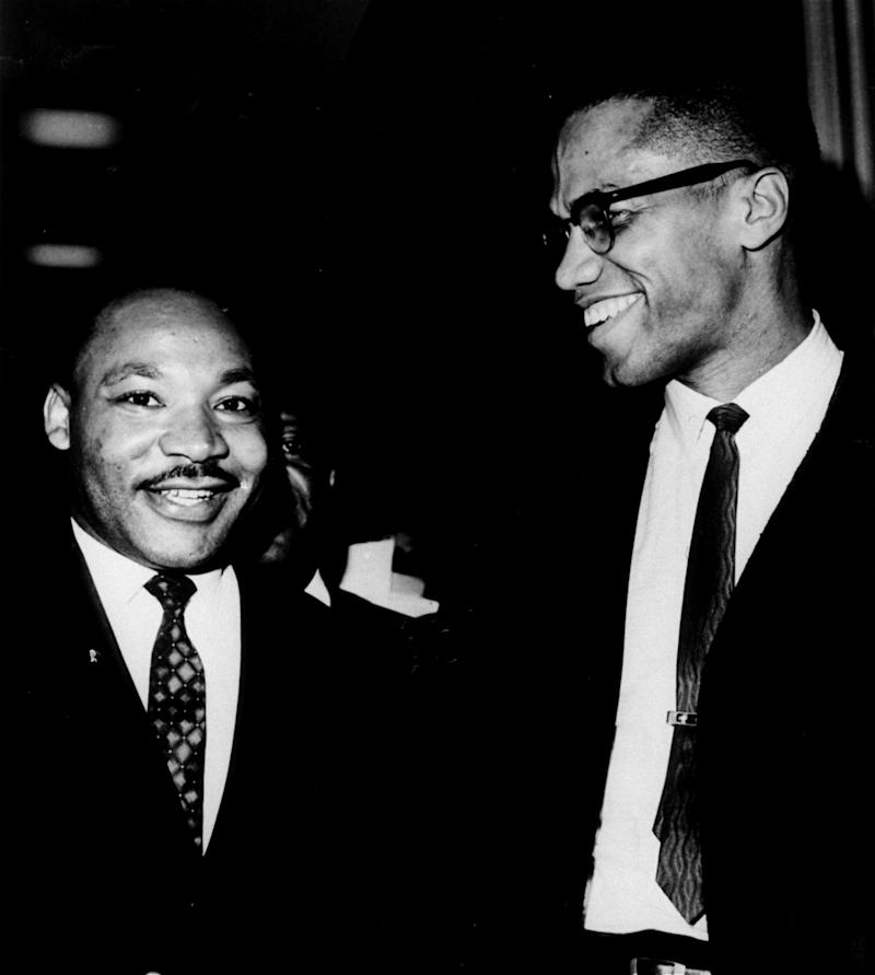 """The Rev. Martin Luther King, Jr., left, of the Southern Christian Leadership Conference, and Malcolm X, head of a new group known as Muslim Mosque, Inc., smile for photographers March 26, 1964, at the Capitol. They shook hands after King announced plans for """"direct action"""" protests if Southern senators filibuster against the civil rights bill. Malcolm X, who has broken with the Black Muslims, predicted another march on Washington if a filibuster against the civil rights drags on. (AP Photo/Henry Griffin)"""