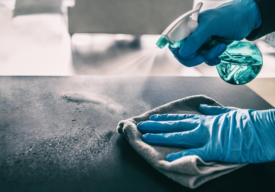 Surface sanitizing against COVID-19 outbreak. Home cleaning spraying antibacterial spray bottle disinfecting against coronavirus wearing nitrile gloves. Sanitize hospital surfaces prevention.