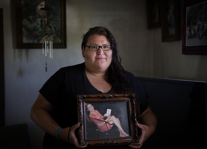 FILE - In this July 13, 2018, file photo, Kimberly Loring stands in her grandmother's home in Browning, Mont., holding a photo of her sister, Ashley Heavyrunner Loring, who went missing on the Blackfeet Indian Reservation. A key congressional committee is holding a hearing on a slate of legislation aimed at addressing the deaths and disappearances of Native American women. The bills before the U.S. Senate Committee on Indian Affairs would require law enforcement to submit annual reports to Congress to give lawmakers a better handle on the number of cases. (AP Photo/David Goldman, File)
