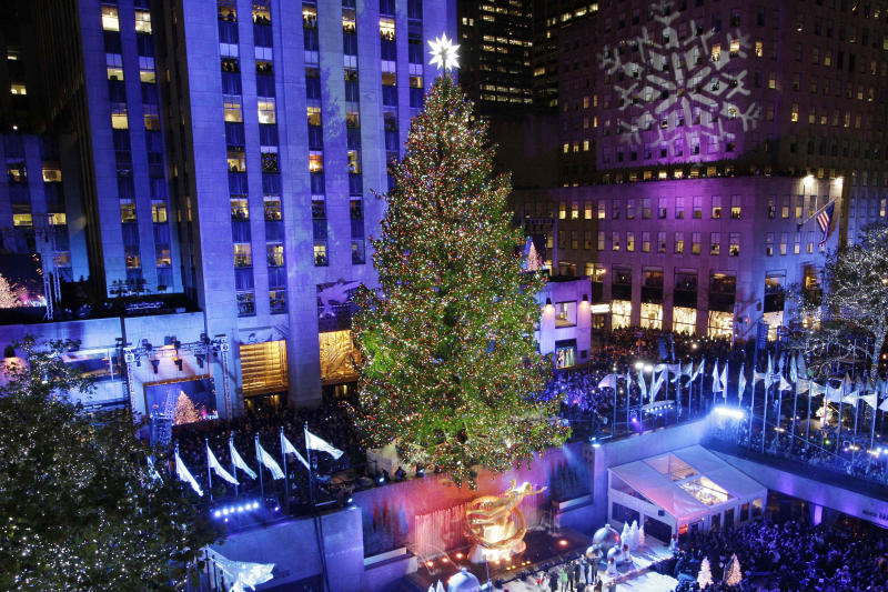 """FILE - In this Wednesday, Nov. 28, 2012 file photo, the Rockefeller Center Christmas tree is lit during the 80th annual tree lighting ceremony at Rockefeller Center in New York. Comcast said Tuesday, Feb. 12, 2013, that it's buying General Electric's 49 percent stake in the NBCUniversal joint venture for $16.7 billion several years early, as the company takes advantage of low borrowing costs and what CEO Brian Roberts called a """"very attractive price.""""(AP Photo/Kathy Willens)"""