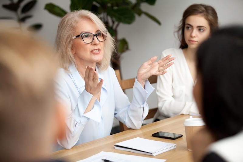 Professionally dressed woman talking and gesturing while other professionals at the same table look on