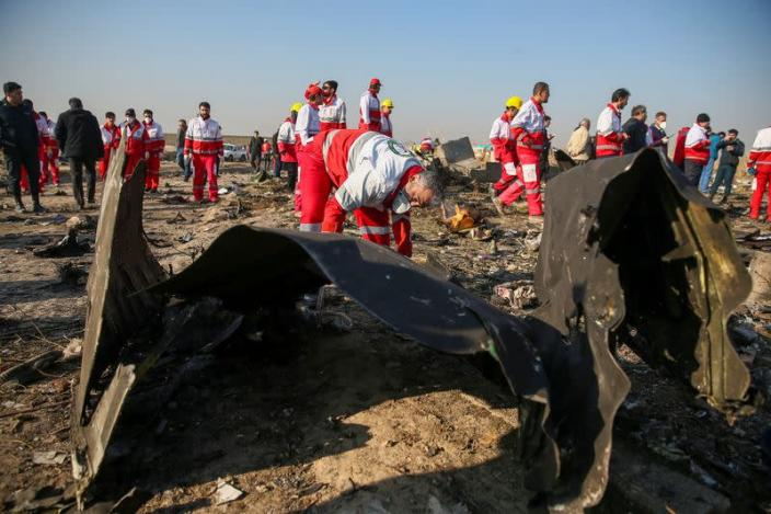 Red Crescent workers check the debris from the Ukraine International Airlines plane, that crashed after take-off from Iran's Imam Khomeini airport, on the outskirts of Tehran