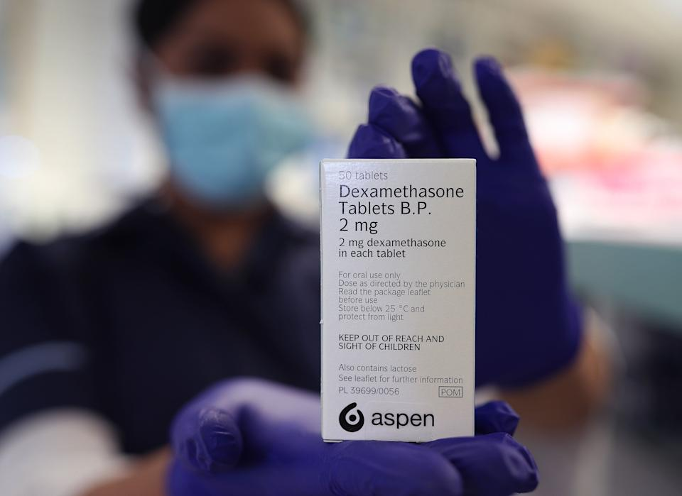 A member of staff at a pharmacy in London holds a packet of anti-inflammatory drug dexamethasone (Photo: PA)