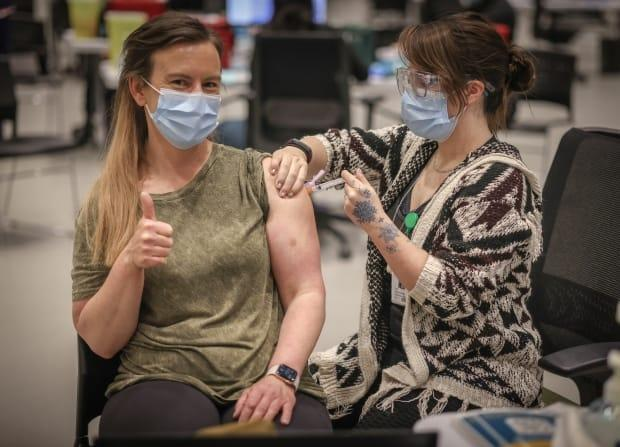 Lana Weatherdon, 43, receives the AstraZeneca vaccine from Lee Buzzell-Lavoie at the Telus Convention Centre immunization site in Calgary on April 20, 2021. As of this week, Albertans as young as 40 can get the shot. (Leah Hennel for AHS - image credit)
