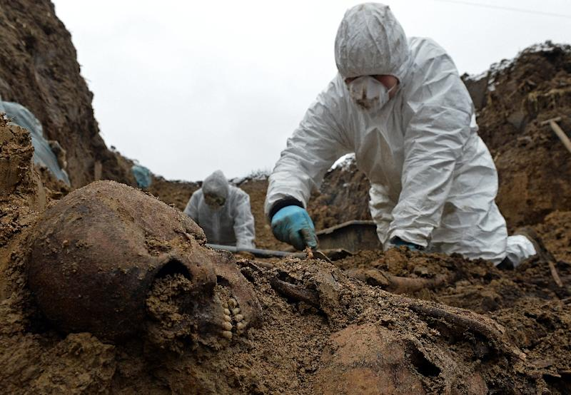 An archeologist digs up remains of one of more than 2500 Soviet and Italian soldiers from World War II who died in a Nazi German stalag near the city of Przemysl, Poland