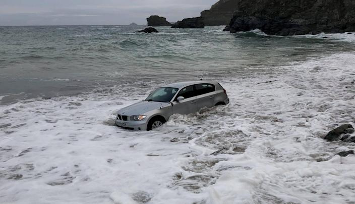 Bizarre pictures show an abandoned silver BMW being washed out to sea on St Agnes beach in Cornwall. (SWNS)