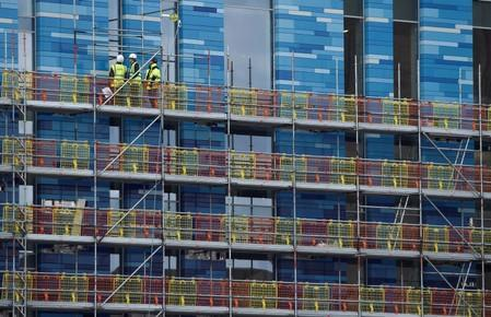 Workers stand on scaffolding at a residential building in London