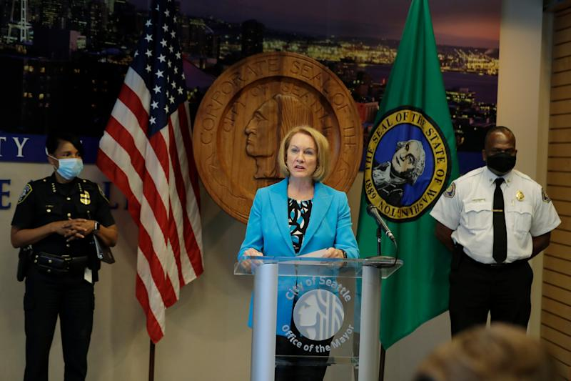 Seattle Mayor Jenny Durkan, center, speaks during a July 13 news conference at City Hall in Seattle as Police Chief Carmen Best, left, and Fire Chief Harold Scoggins , right, look on.