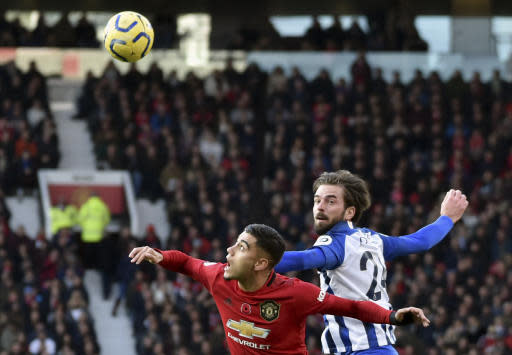 Manchester United's Andreas Pereira, left, jumps for the ball with Brighton's Davy Proepper during the English Premier League soccer match between Manchester United and Brighton and Hove Albion, at the Old Trafford stadium in Manchester, England, , Sunday, Nov. 10, 2019. (AP Photo/Rui Vieira)