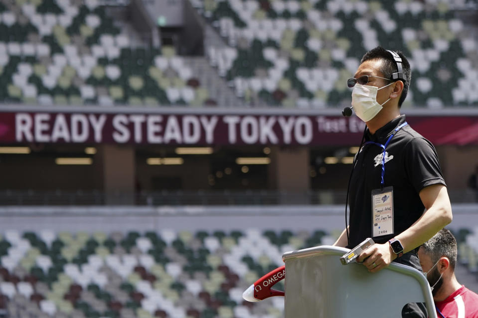 FILE - In this May 9, 2021, file photo, an official wearing a face mask waits to use a starter pistol for a women's 100 meter heat at an athletics test event for the Tokyo 2020 Olympics Games at National Stadium in Tokyo. The Tokyo Olympics are not looking like much fun: Not for athletes. Not for fans. And not for the Japanese public, who are caught between concerns about the coronavirus at a time when few are vaccinated on one side and politicians and the International Olympic Committee who are pressing ahead on the other. (AP Photo/Shuji Kajiyama, File)