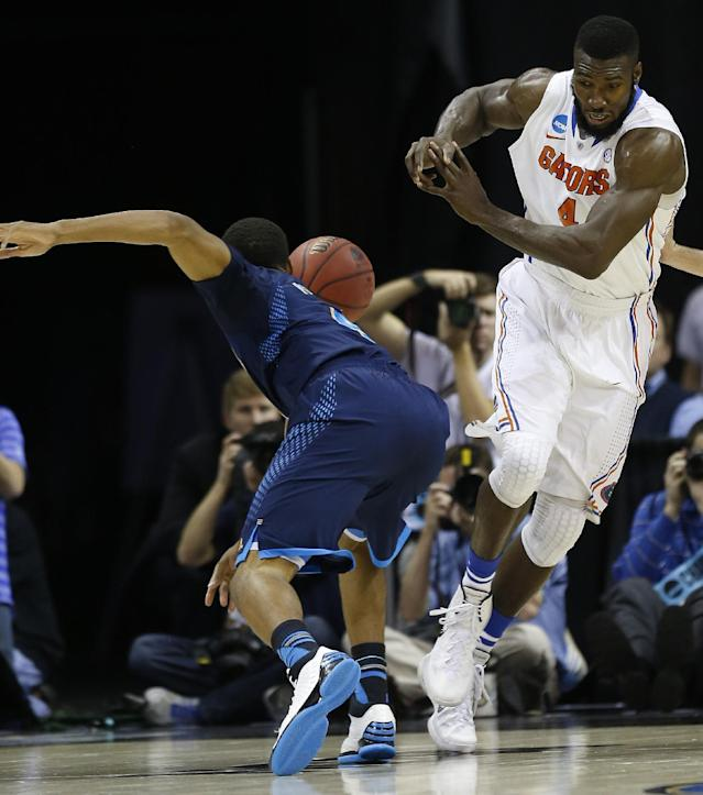 Florida center Patric Young (4) collides with UCLA guard Norman Powell (4) during the first half in a regional semifinal game at the NCAA college basketball tournament, Thursday, March 27, 2014, in Memphis, Tenn. (AP Photo/John Bazemore)