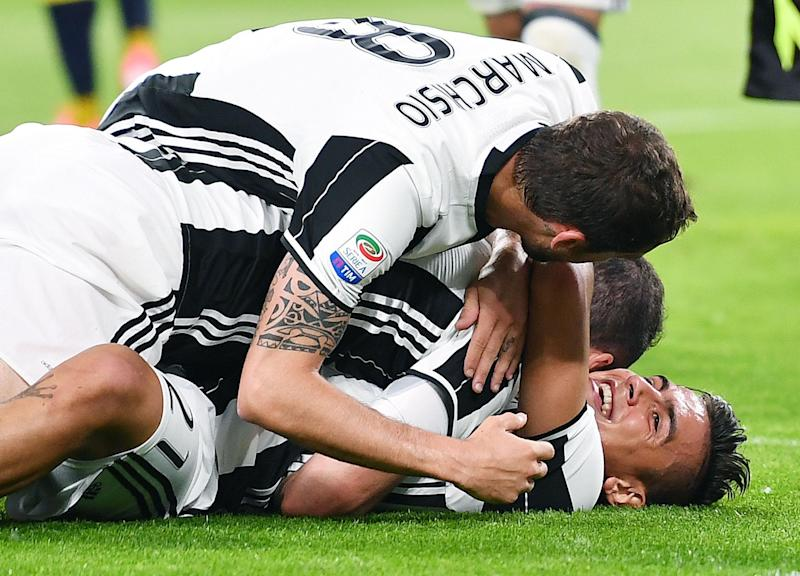 Juventus' Gonzalo Higuain celebrates with his teammate Paulo Dybala, bottom, after scoring a goal during the Italian Serie A soccer match between Juventus and Chievo Verona at the Juventus Stadium in Turin, Italy, Saturday, April 8, 2017. (Alessandro Di Marco/ANSA via AP)