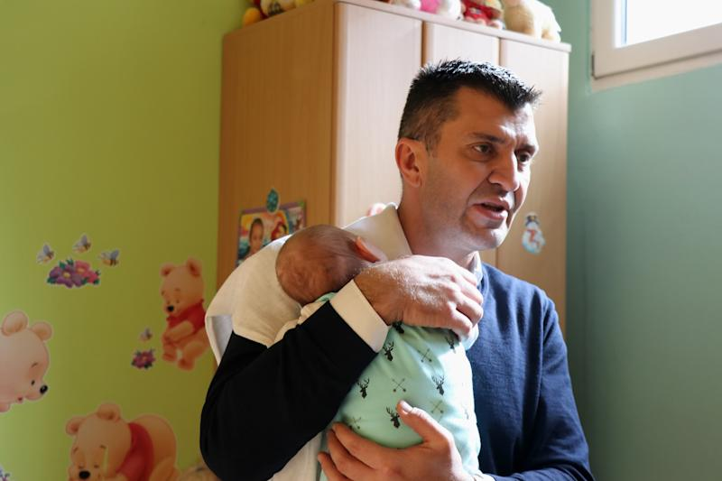 Serbian Minister of Labor, Employment, Veterans' Affairs and Social Affairs Zoran Djordjevic carries baby Stefan in his arms.