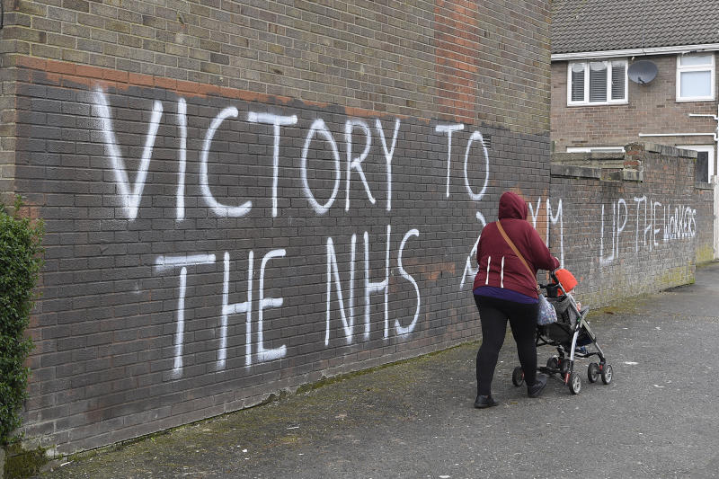 A woman walks past a message of support for the NHS in Londonderry, as the UK continues in lockdown to help curb the spread of the coronavirus. (Photo by Michael Cooper/PA Images via Getty Images)