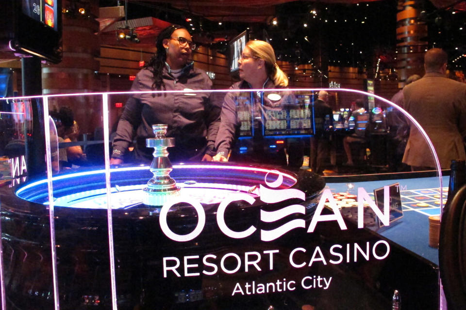 Dealers wait for customers at a roulette table at the Ocean Casino Resort in Atlantic City N.J., on June 18, 2019. In a lawsuit filed Thursday, Aug. 27, 2020, Atlantic City's top casino, the Borgata, accuses Ocean Casino Resort of poaching its top marketing executives, including one with a cell phone containing priceless information on the Borgata's top customers, who spend $1.5 million to $4 million per visit. (AP Photo/Wayne Parry)