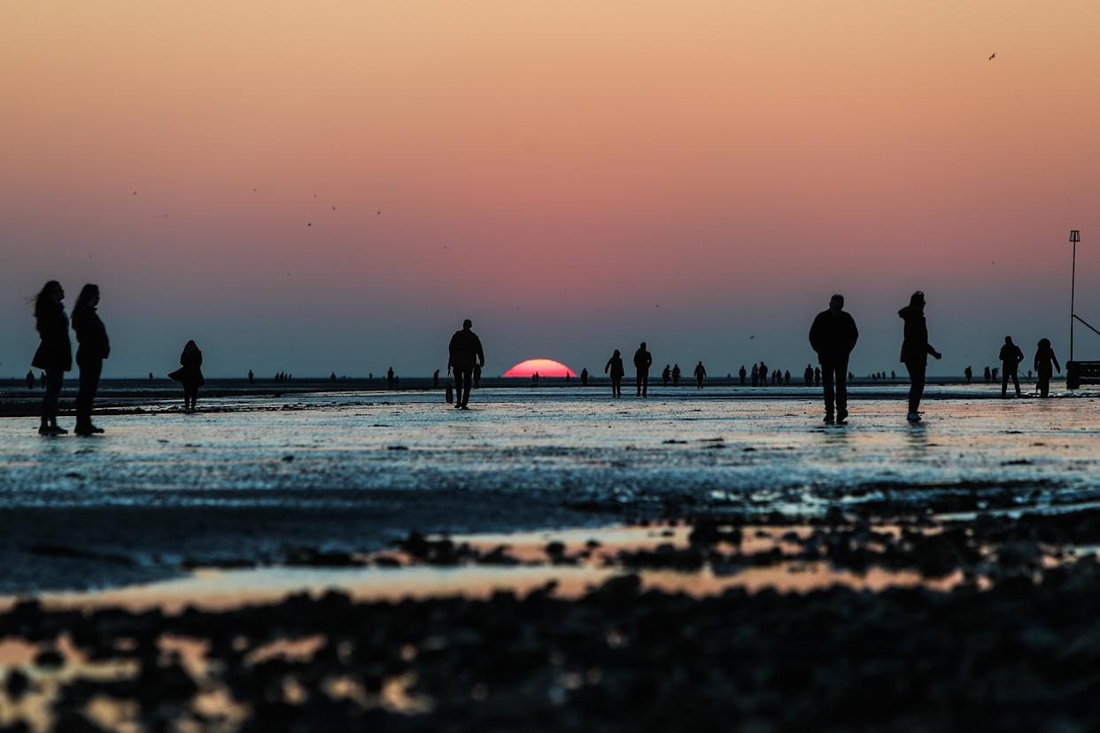 People walk along Worthing beach, Sussex, while watching the sunset. Picture date: Sunday February 28, 2021.
