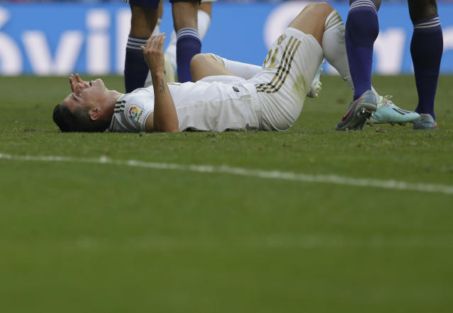 Real Madrid's James Rodriguez lies on the field during the Spanish La Liga soccer match between Real Madrid and Valladolid at the Santiago Bernabeu stadium in Madrid, Spain, Saturday, Aug. 24, 2019. (AP Photo/Paul White)